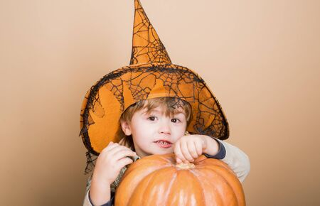 Happy Halloween. Carnival costume. Jack o lantern. Toddler in witch hat. Halloween pumpkin. Preparation for Halloween party. Boy dressed up trick or treating. Kid with pumpkin. Kid trick or treat