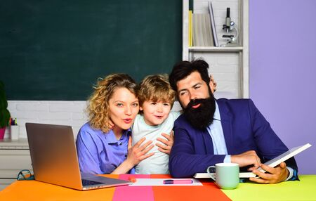School concept. School boy in first grade. Happy family schooling math together. Cute pupil and his father and mother making homework. Little boy and his parents. Education for children. September 1