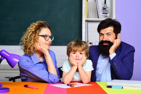 School boy in first grade. Happy family schooling math together. Cute pupil and his father and mother making homework. Little schoolboy and his parents. Home schooling. September 1. Ready to study 版權商用圖片