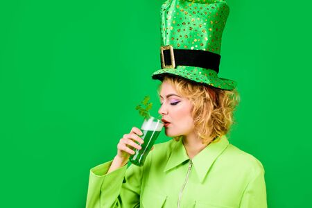 St Patrick's Day. Woman drinking in pub. Green top hat. Saint Patrick. Woman in top hat drinking beer. Green beer. 免版税图像