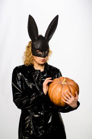 Sensual girl in bunny mask with jack o lantern. Woman in black bunny mask. Beautiful sexy girl in Halloween party. Surprised blonde woman in halloween bunny costume holding pumpkin. Halloween costume 免版税图像