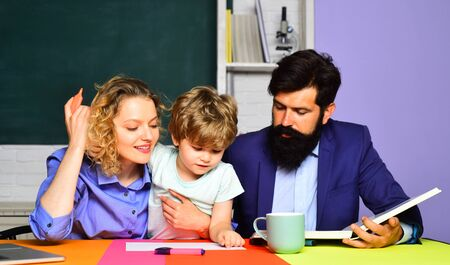 Home family schooling. Mathematics for kids. Schoolboy learning letters and numbers with parents. Parents teaching kid private lessons in math. Back to school. Home schooling. Parents helps child boy