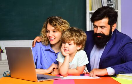 Schoolboy learning letters and numbers with parents. Parents teaching kid private lessons in math. Back to school. Home schooling. Home family schooling. Mathematics for kids. Parents helps child boy Stock Photo