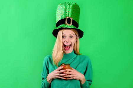 Saint Patrick's Day. Happy girl in green top hat holds pot with gold. Leprechaun. Irish Traditions. Green top hat. Green hat with clover. Clover. Patrick's Day. Pot with gold. Gold.
