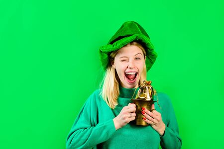 Green top hat. Blonde girl in Leprechaun costume holds bag with gold. Leprechaun. Bag with gold. Green leprechaun. Green hat with clover. Saint Patrick's Day - Celebrations Traditions. Saint Patrick.