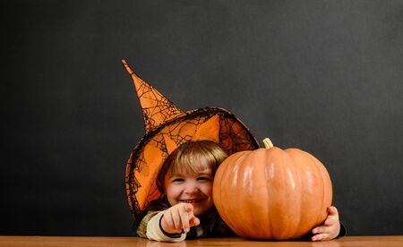 Smiling boy in witch hat with halloween pumpkin pointing to you. Trick or treat. Child with pumpkin. Preparation Halloween holiday. Happy Halloween. Autumn. Halloween party. Witch costume. 31 October