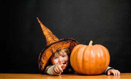 Truco o trato. Niño con calabaza. Preparación fiesta de Halloween. Feliz Halloween. Otoño. Fiesta de Halloween. Disfraz de bruja. 31 de octubre. Niño con sombrero de bruja con calabaza de halloween apuntando hacia ti
