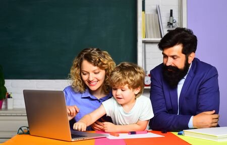 Beginning of lessons. School concept. Happy family. Woman and man helps the child boy. First time to school. Young happy family schooling math together. Children Education and Pupils Education Stock Photo - 128950972