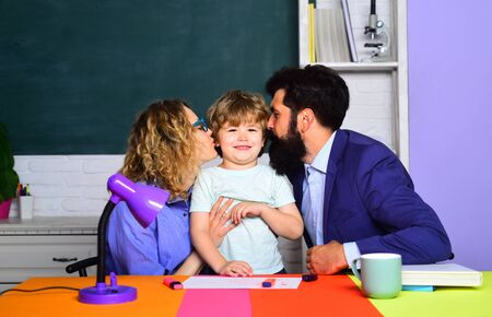 Happy parents kissing little child. Mom and dad kissing his son. Cute pupil and his parents making schooling work. First time to school. Children education. Parenting. Happy family schooling together