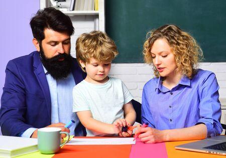 Familienunterricht zu Hause. Eltern geben ihren Kindern Privatunterricht in Mathe. Zurück zur Schule. Heimunterricht. Mathematik für Kinder. Schüler lernen Buchstaben und Zahlen mit den Eltern. Eltern helfen Kind Junge