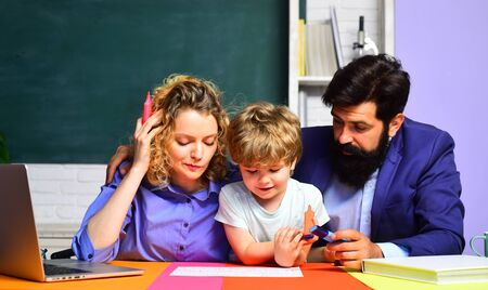 Parents teaching kids private lessons in math. Home family schooling. Back to school. Home schooling. Mathematics for kids. Pupil learning letters and numbers with parents. Parents helps child boy