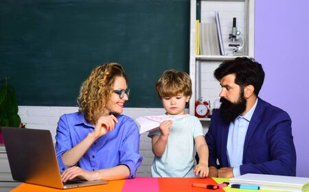 Mathematics for kids. Home schooling. Parents helps child boy. Home family schooling. Schoolboy learning letters and numbers with parents. Parents teaching kid private lessons in math. Back to school