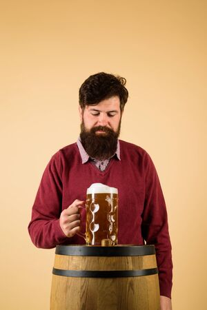 Equipment for preparation of beer. Brewery concept. Man tasting draft beer. Beer pub and bar. Man holds mug of beverage. Happy brewer holds glass with ale. Brewer. Handsome bearded man drinking beer
