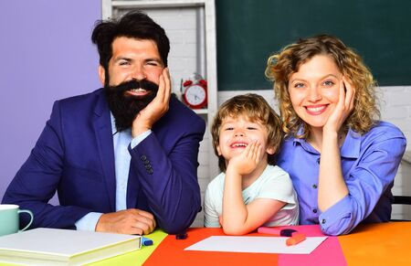 Parents teaching kids private lessons in math. Back to school. Home schooling. Home family schooling. Mathematics for kids. Pupil learning letters and numbers with parents. Parents helps child boy Stock Photo - 128955247