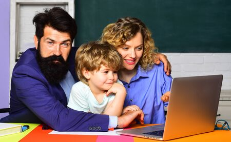 Mathematics concept. Little boy ready to study. Pupil learning letters and numbers. Elementary student. Happy family. Woman and man helps child. First time to school. Parenting. Mathematics for kids Stock Photo - 128955275