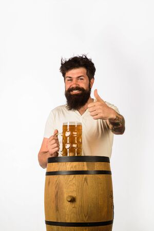 Wooden barrel and glass of beer. Oktoberfest. Bearded man with glass of beer shows thumb up. Germany traditions. Man holding mug of beer. Concept of craft beer. Thumb up