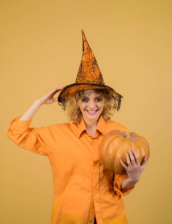 Attractive model girl in Halloween costume. Halloween decoration and scary concept. 31 October. Party and traditional food. Halloween pumpkin. Halloween party girl. Beautiful witch with bright makeup
