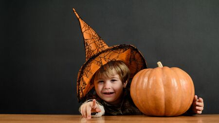 Cute little witch with pumpkin. Children in Halloween costumes with pumpkin fooled on holiday. Witch. Witcher. Hag. Beldam. Nightmare. Charmer. Magician. Mage. Wizard