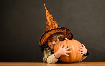 Cute little witch hugs pumpkin. Child in Halloween costumes with pumpkin. Witch. Witcher. Hag. Beldam. Nightmare. Charmer. Magician. Mage. Wizard. Trick or treat. Halloween. 31 October