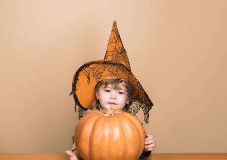 31 October. Cute boy in witch hat with halloween pumpkin jack o lantern. Trick or treating. Magic pumpkin. Autumn. Halloween party. Preparation Halloween holidays. Child with pumpkin. Happy Halloween