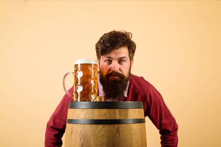 Brewer. Serious bearded man with lager beer. Equipment for preparation of beer. Brewery concept. Man tasting draft beer. Beer pub and bar. Man holds mug of beverage. Happy brewer holds glass with ale
