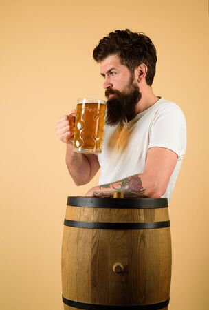 Man tasting draft beer. Beer pub and bar. Brewery concept. Man holds mug of beverage. Happy brewer holds glass with ale. Brewer. Handsome bearded man drinking beer. Equipment for preparation of beer