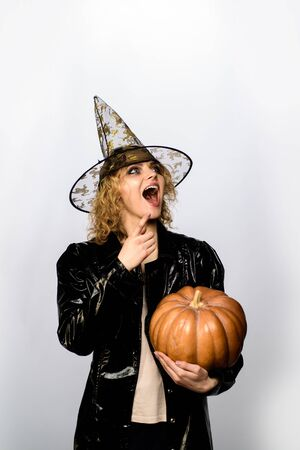 Halloween costume for party. Halloween holidays. 31 October. Woman in witch hat with pumpkin. Happy woman in witch halloween costume with jack o lantern. Girl witch with pumpkin. Happy Halloween Reklamní fotografie