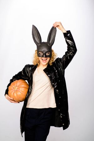 Smiling girl in Halloween party. Sexy girl in bunny mask with jack o lantern. 31 October. Woman in black bunny mask. Halloween costume. Beautiful blonde woman in halloween bunny costume with pumpkin 免版税图像