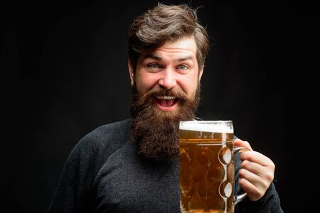 Enjoy in pub. Happy brewer. Celebration oktoberfest festival concept. Man in beer pub. Bearded man holds mug of craft beer. Brewery concept. Happy smiling man with beer. Alcohol, harmful habits