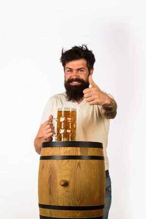 Wooden barrel and glass of beer. Oktoberfest. Bearded man with glass of beer shows thumb up. We meet oktoberfest. Germany traditions. Man holding mug of beer. Concept of craft beer. Thumb up