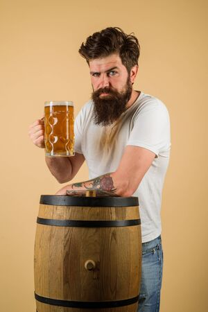 Man tasting draft beer. Man holds mug of beverage. Happy brewer holds glass with ale. Brewer. Handsome bearded man drinking beer. Equipment for preparation of beer. Beer pub and bar. Brewery concept Banco de Imagens - 129288015