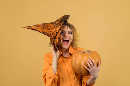 Happy young woman in witch halloween costume with hat. Surprised woman holds pumpkin. Halloween concept. Halloween Witch with magic pumpkin. Beautiful woman in witches hat and costume holds pumpkin Reklamní fotografie