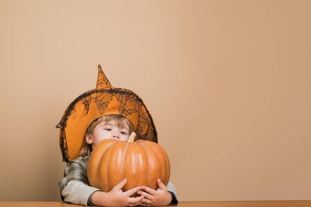 Happy Halloween. Cute boy in witch hat hugging halloween pumpkin. Jack o lantern. Trick or treat. Halloween party. Preparation for Halloween holidays. Child with pumpkin.