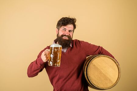 Bearded man hold glass and barrel with craft beer. Attractive bearded brewer with wooden barrel of beer and mug of beer. Oktoberfest festival. Holliday, drinks, alcohol and leisure concept. Beer time Stock Photo
