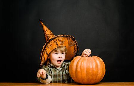 Feliz Halloween. Fiesta de Halloween. Niño con calabaza. Niño con sombrero de bruja con calabaza de halloween apuntando hacia ti. Truco o trato. Preparación fiesta de Halloween. Niño disfrazado de truco o trato