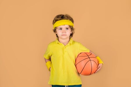 Boy with basketball ball. Cute little basketball player training. Children and sport. Little basketball player in sportswear holds ball. Small boy in sport uniform playing basketball. Sport equipment Standard-Bild - 129946233