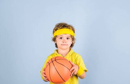 Cute little basketball player training. Children and sport. Little basketball player in sportswear holds ball. Small boy in sport uniform playing basketball. Sport equipment. Boy with basketball ball Standard-Bild - 129946236