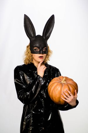 Thoughtful young girl in black halloween costume. Serious woman in bunny mask with pumpkin. Sexy girl in Halloween party. Woman in bunny mask with jack o lantern. 31 October. Halloween bunny costume Фото со стока