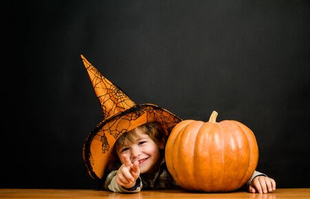 Niño de Halloween apuntando al frente. Niño con calabaza apuntando hacia ti. Niño con sombrero de bruja con calabaza de halloween muestra el dedo sobre ti. Truco o trato. Preparación fiesta de Halloween. fiesta de Halloween