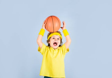 Little basketball player in sportswear trows ball. Small boy in sport uniform playing basketball. Sport equipment. Boy with basketball ball. Cute little basketball player training. Children and sport Standard-Bild - 129947963