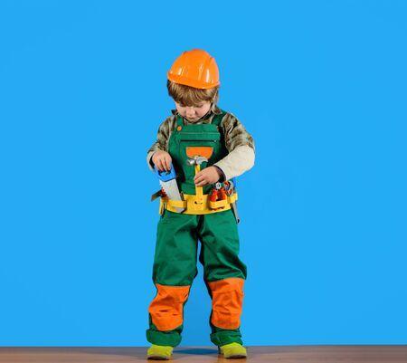 Work with tools. Little boy in builders uniform with repair tools. Repair. Boy as builder or repairer. Tools for building. Builder boy in helmet and tools. Little repairman with tool belt. Child game