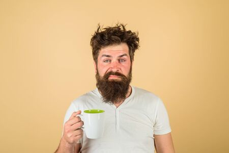 Morning refreshment and drink. Breakfast concept. Bearded man with white coffee cup. Tired sleepy man with beverage in cup. Handsome bearded young man drinking coffee or tea. Refreshment and energy 写真素材