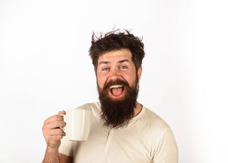 Refreshment and energy. Morning coffee concept. Cheerful man having cup of coffee in kitchen. Happy man holds mug with hot drink. Inspired with cup of fresh coffee. Smiling bearded man holds tea mug