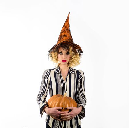 31 October. Sensual girl in witch halloween costume. Happy Halloween. Serious girl witch with pumpkin. Woman in witch hat with pumpkin. Jack o lantern. Halloween holidays. Halloween costume for party