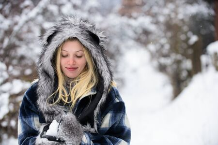 Girl playing with snow. Season of winter. Wintertime. Smiling woman in warm clothing with snowball. Beautiful young woman in winter. Girl in mittens hold snowball. Happy woman holds snowball in hands