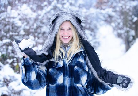 Girl in mittens hold snowball. Girl playing with snow. Smiling woman in warm clothing with snowball. Beautiful young woman in winter. Season of winter. Wintertime. Happy woman holds snowball in hands Zdjęcie Seryjne