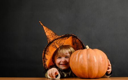 Preparation Halloween holiday. Cute kid boy in witch hat with halloween pumpkin pointing to you. Trick or treat. Happy Halloween. Halloween party. Witch costume. 31 October. Boy with pumpkin. Autumn