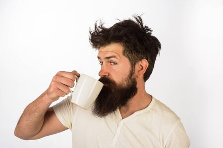 Good morning. Handsome bearded man drinking cup of hot beverage. Morning with coffee or milk. Man with cup of coffee. Bearded man with mug in hand. Morning coffee concept. Businessman drinking coffee