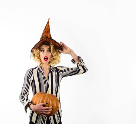 31 October. Surprised girl in witch halloween costume. Happy Halloween holidays. Amazed girl witch with pumpkin. Woman in witch hat with pumpkin. Jack o lantern. Magic witch hat. Magic Pumpkin Stock Photo