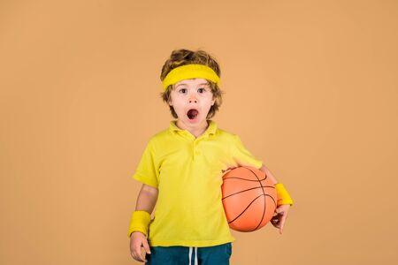 Cute boy holds basketball ball. Adorable child playing basketball. Basketball player with ball. Little kid with basket ball. Basketball boy. Little basketballer. Child boy in sportswear holds ball